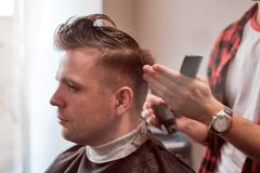 Caucasian young man in Barbershop. Barber is cuttinhg his hair in hipster style. Royalty Free Stock Photography