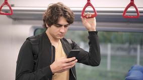 Man riding in train and using his smartphone