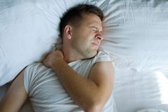 Caucasian young man having terrible pain in neck in bed in the morning. Concept pf health problems with muscles stock photo