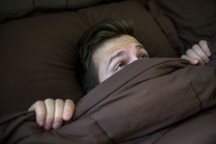 Caucasian young man hiding in bed under the blanket at home. He is stressed and tries run away from problems Stock Image
