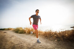 Caucasian young man running on a seacost path Royalty Free Stock Photos