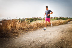 Caucasian young man running on a seacost path Royalty Free Stock Images