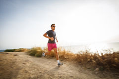 Caucasian young man running on a seacost path Stock Photo