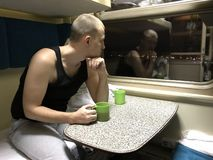 Caucasian young man sits at table in train car, holds green cup of tea and looks thoughtfully out window at lights of night city stock photos