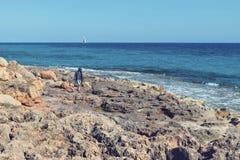 Caucasian young man walking on a rocky coast in Cap de Ses Salin. Majorca royalty free stock images