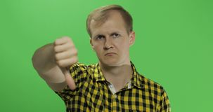 Caucasian young man in yellow shirt showing no and giving his thumb down stock photos
