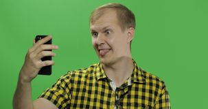Caucasian young man in yellow shirt taking funny selfies on the smartphone royalty free stock photos