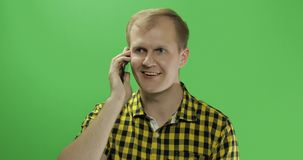 Caucasian young man in yellow shirt using mobile phone for call royalty free stock photography