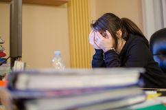 Stressed woman at work with computer in front of her. Caucasian young stressed young girl at work with computer falling into burn out Royalty Free Stock Photo