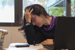Stressed woman at work with computer in front of her. Caucasian young stressed young girl at work with computer falling into burn out Royalty Free Stock Photos