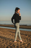 Caucasian young woman in black sweat shirt, blue jeans walking alone on beach in the sunset. Outdoor portrait pensive or Stock Photography