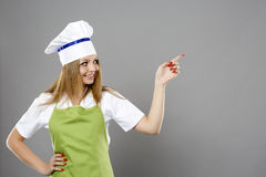 Caucasian young woman chef pointing direction Stock Images