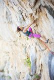 Young woman climbing challenging route on overhanging cliff. Caucasian young woman climbing challenging route on overhanging cliff royalty free stock photography