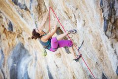 Young woman climbing challenging route on overhanging cliff. Caucasian young woman climbing challenging route on overhanging cliff stock photography