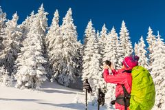 Caucasian young woman in colorful outfit taking a break from bac. Caucasian woman in colorful outfit taking a break from backcountry skiing taking a picture Royalty Free Stock Images