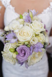 Caucasian young woman dressed in white, holding a large bridal flower arrangement for the big day royalty free stock photos