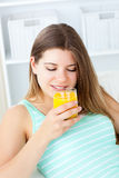 Caucasian young woman drinking orange juice stock photography