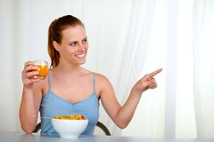 Caucasian young woman eating and pointing Stock Images