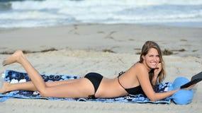 Caucasian young woman laying on beach in bikini Stock Image