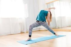 Caucasian young woman practicing virabhadrasana, high lunge asana. On exercise mat indoor royalty free stock photos