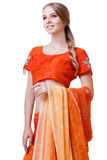 Caucasian young woman in red indian national dress isolated. Caucasian blonde smiling girl in red indian national dress sari in studio on white background Stock Image