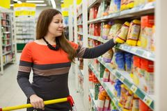 Caucasian young woman with shopping cart selects cereals on store counter Royalty Free Stock Photos