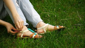 Caucasian young woman sitting on the grass in the park buttons their sandals. Footage girl relaxing outdoor stock video
