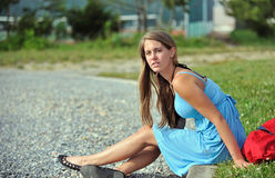 Caucasian young woman sitting by a gravel road Stock Images