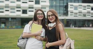 Two happy caucasian young women best friends having fun wearing trendy sunglasses, posing outdoor, looking at camera. Caucasian young women best friends having stock video footage