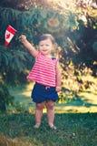 Caucasianen behandla som ett barn den hållande kanadensiska flaggan för flickan med den röda lönnlövet Royaltyfria Bilder