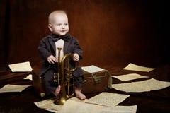 Caucasianen behandla som ett barn pojkelekar med trumpeten Royaltyfria Bilder