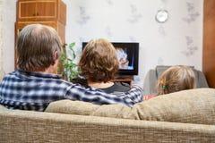 Caucasianföräldrar och dottersammanträde på soffan och hållande ögonen på tv, bakre sikt Arkivbilder
