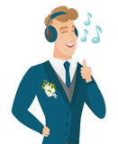Caucasiangroom listening to music in headphones. Stock Photo