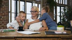 Caucasiano da mulher envelhecida média que trabalha com documentos de papel quando seus netos bonitos dos adolescentes que entram filme