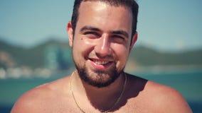Caucasiano novo do retrato ascendente próximo do homem moreno considerável uma barba que olha nos sorrisos da câmera, no fundo do filme