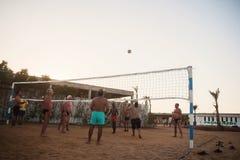 Caucasians masculinos, árabes, africanos que jogam o voleibol na praia foto de stock