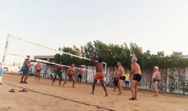 Caucasians masculinos, árabes, africanos que jogam o voleibol na praia fotografia de stock