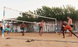 Caucasians masculinos, árabes, africanos que jogam o voleibol na praia fotografia de stock royalty free