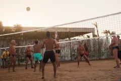 Caucasians masculinos, árabes, africanos que jogam o voleibol na praia fotos de stock royalty free