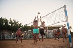 Caucasians masculinos, árabes, africanos que jogam o voleibol na praia no por do sol Egypt Hurghada O 5 de outubro dourado 7, 201 fotografia de stock