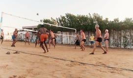 Caucasians masculinos, árabes, africanos que jogam o voleibol na praia no por do sol Egypt Hurghada O 5 de outubro dourado 7, 201 fotografia de stock royalty free