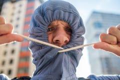 Caucasianyoungs-Mann, der unrasiertes Gesicht mit Haube versteckt Geheimhaltung und Geheimnis Stockbild