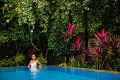 Caucasican woman rests in blue pool in tropics Royalty Free Stock Photos