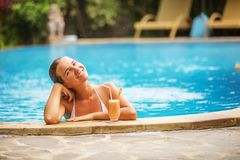 Caucasican woman rests in blue pool in tropics Stock Photo