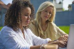Caucasien féminin de deux amis et travail Afro ensemble dehors au café d'Internet frais avec l'ordinateur portable en tant que tr Photographie stock libre de droits