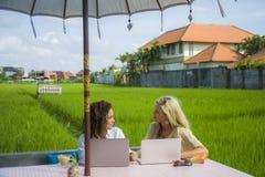 Caucasien féminin de deux amis et travail Afro ensemble dehors au café d'Internet frais avec l'ordinateur portable en tant que tr Image libre de droits