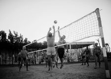 Caucasiens masculins, Arabes, Africains jouant le volleyball sur la plage Image stock