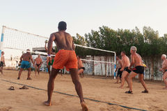 Caucasiens masculins, Arabes, Africains jouant le volleyball sur la plage Images stock