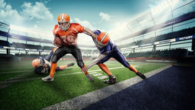 Caucasion american football players in the action on stadium. Young and strong american football players in the action on stadium on green grass Royalty Free Stock Photography