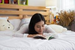 Caucasion della giovane donna che si trova sul rilassamento del libro di lettura del letto Fotografia Stock